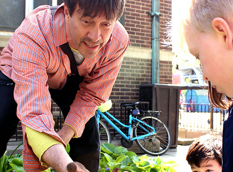 An adult with short hair and pink shirt showing something in his hand to a group of children in a garden