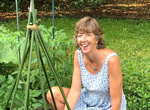 Miriam Snell. Miriam is smilling in a blue dress on a field of plants.