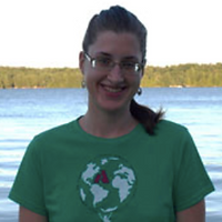 Christine Miller, a winner of 2012. Christine is smiling with a pair of glasses and dark long hair and in a green shirt. Christine is in front of a lake.