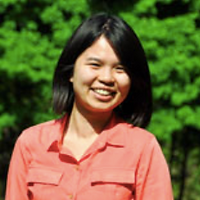 Cynthia Chan, a winner of 2014. Cynthia is smiling with short dark hair and in an orange shirt. Cynthia is in front of a green plant background.