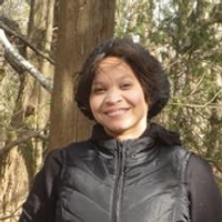 Danielle Feanny, Runner Up, a winner of 2018. Danielle is smiling with dark short hair and a black jacket in front of a tree.