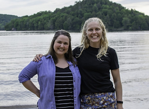 Alberta Robinet and Adrienne Rinne. They are smiling in front of a lake and a hill.