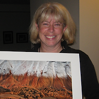 Cathy Dykstra, the Grand Prize Winner of 2015. Cathy is smiling with short hair and a picture in front of them.