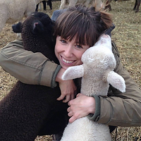 Alicia Belvedere, the Grand Prize Winner in 2017. Alicia is smiling with brown hair tied back, holding an animal in the arm