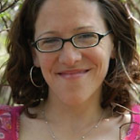 Kimberley Frye, a winner of 2012. Kimberley is smiling with a pair of glasses and brown short curly hair.