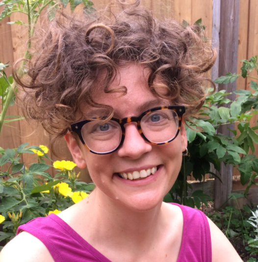 Velvet Lacasse, grand prize winner of the Natural Curiosity Burtynsky award in 2020; she is smiling with short curly hair and a pair of glasses.