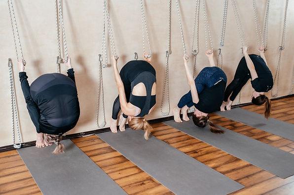 lyengar-grupo-femenino-yogui-practicando-ejercicios-calistenia-estudio-yoga-colgado-pared_