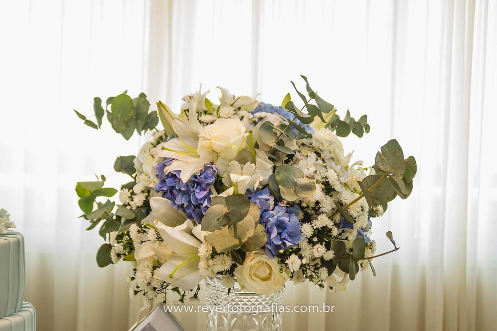 arranjo de flores branca, bege e azul decorando um batizado