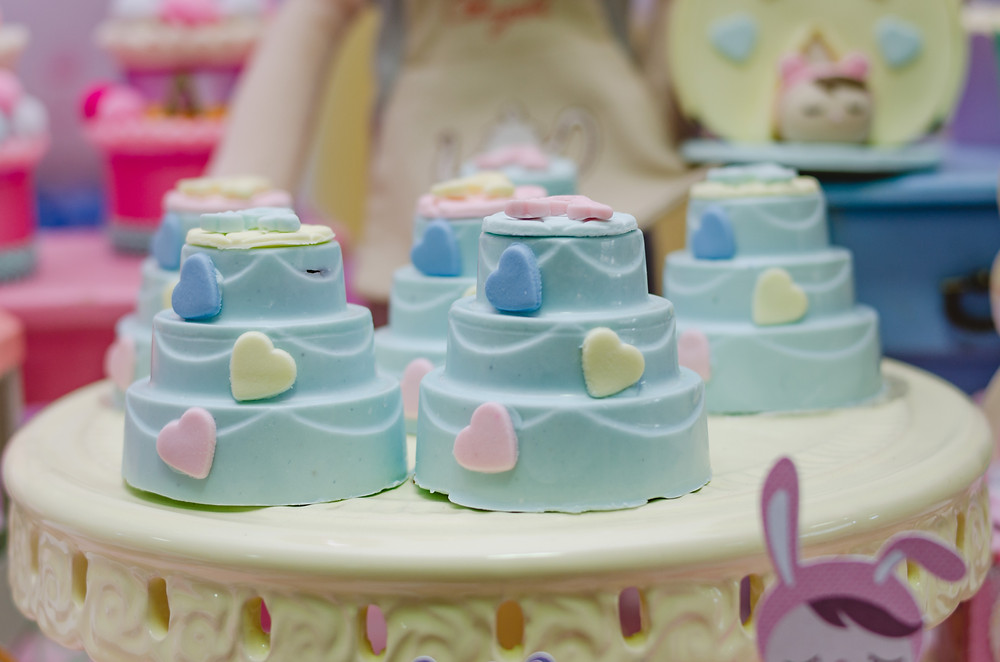 fotografia de doces decorados com corações azul rosa amarelo