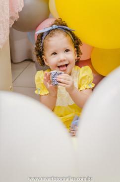 rever fotografias: foto criativa e espontanea de bebe sorrindo em meio aos balões segurando um doce e se escondendo de sua mãe em festa de aniversário infantil de 2 anos com tema da boneca metoo realizada no salão de festas de condominio no bairro jardins na cidade de aracaju sergipe