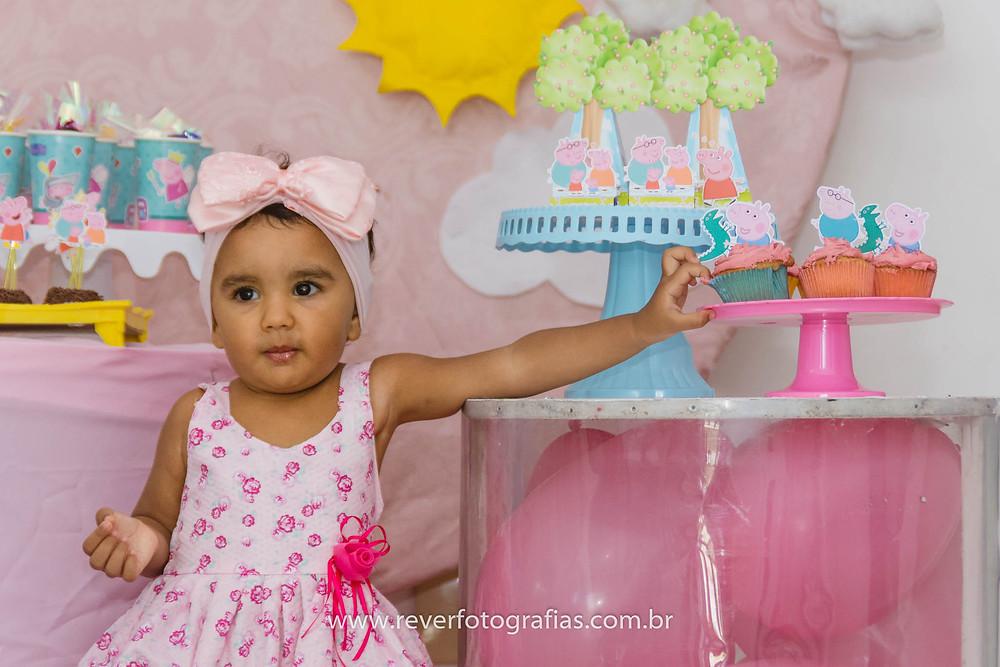 fotografia de criança colocando a mão em cupcake na festa de aniversario