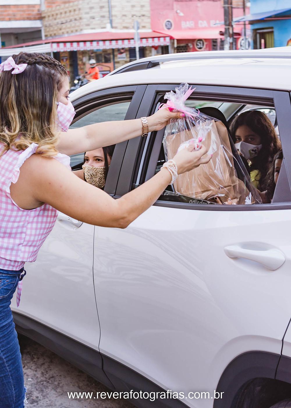 mulher entregando lembrancinhas de festa infantil pela janela do carro na festa drive thru em aracaju