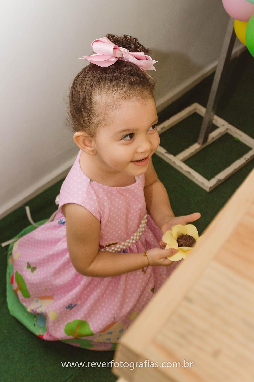 fotografia de menina se escondendo atrás da mesa em festa infantil