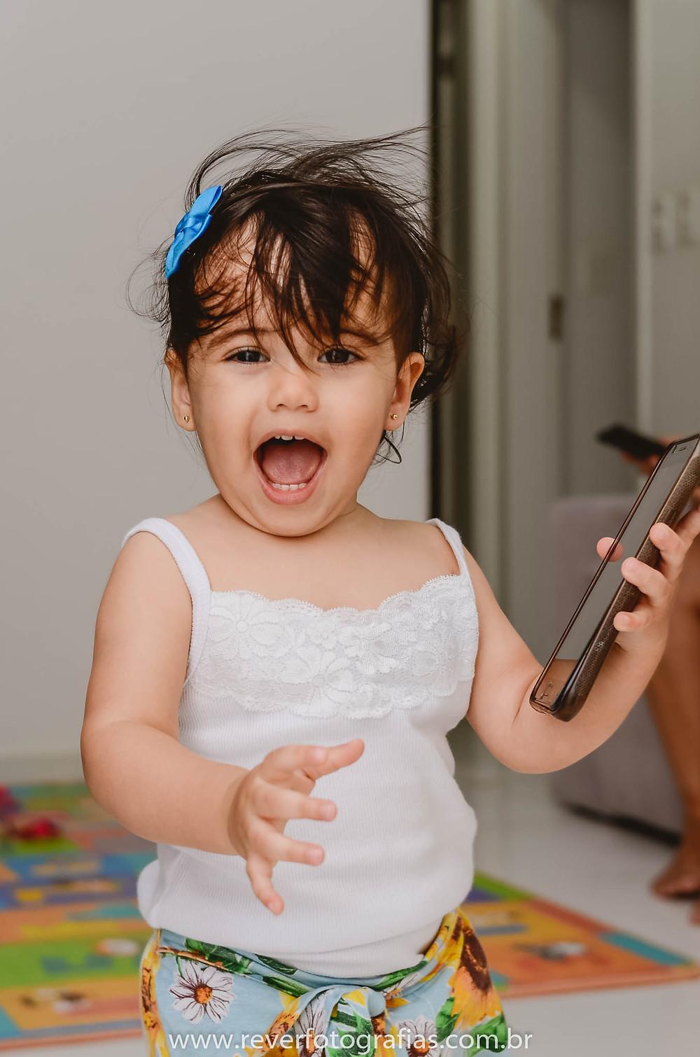 rever fotografias: criança brincando com celular e sorrindo