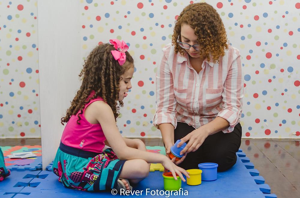 Rever fotografias: sessão de terapia comportamental criança brincando com terapeuta em consultório em Aracaju