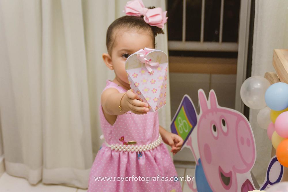 fotografia de menina segurando caixinha de doces em festa infantil da peppa pig