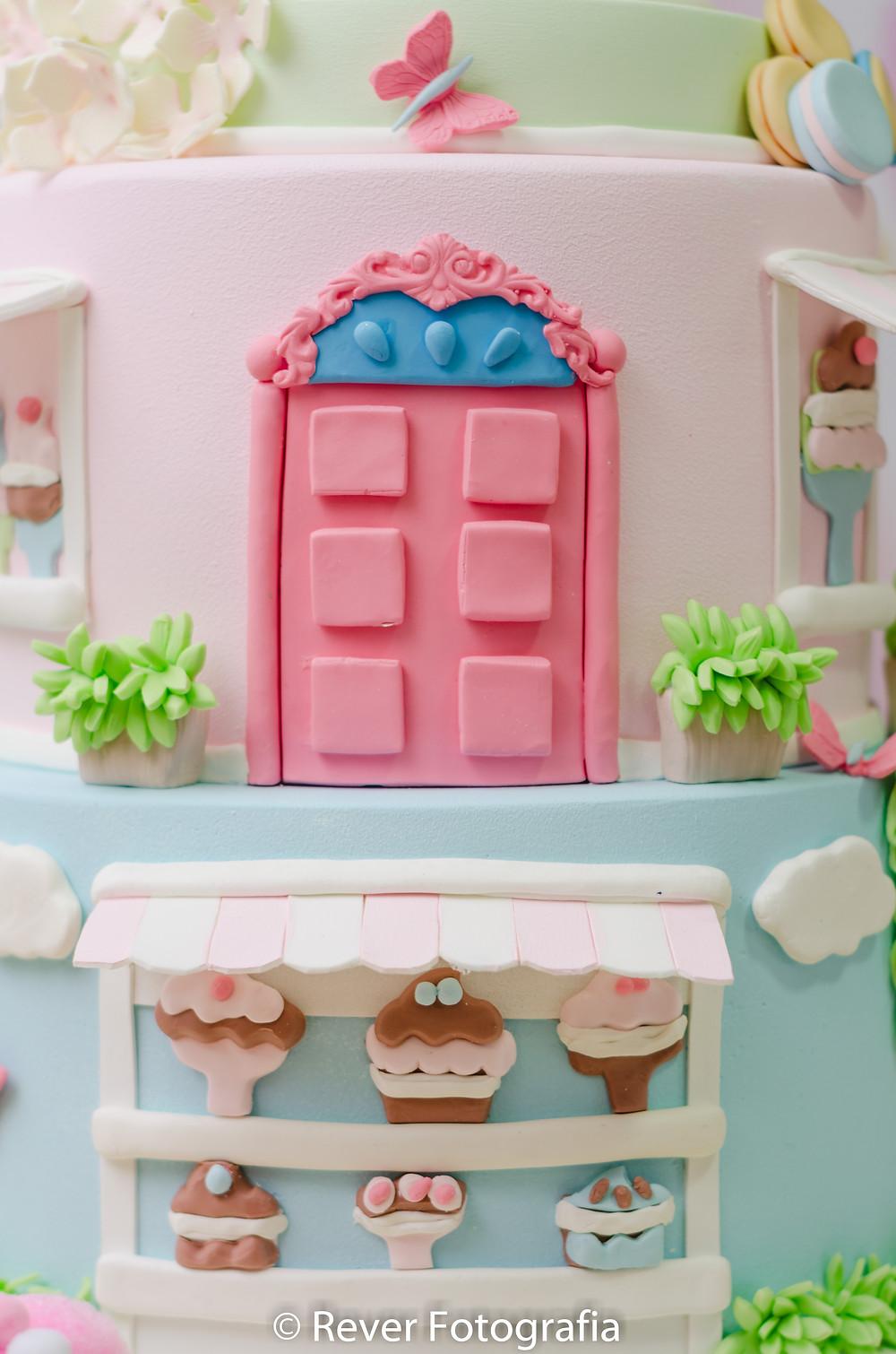 fotografia de bolo decorado em azul rosa e verde com doces em tons pastéis