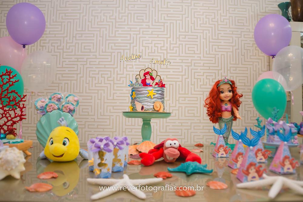 fotografia de mesa de festa infantil decorada com tema da princesa ariel