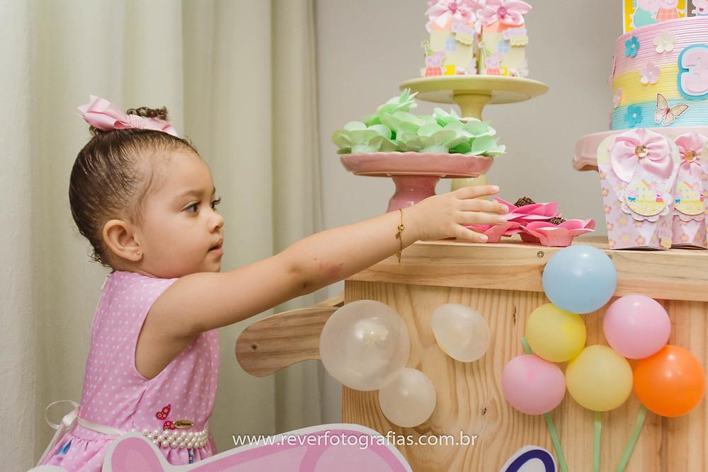 fotografia de menina segurando brigadeiro em festa infantil