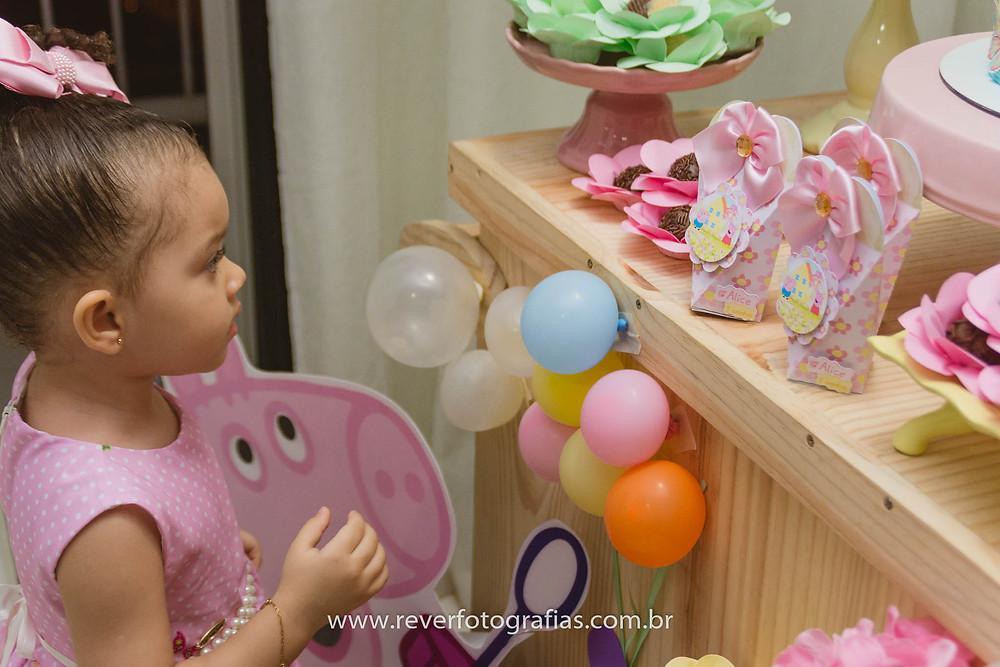 fotografia de criança olhando para mesa decorada com tema da peppa pig