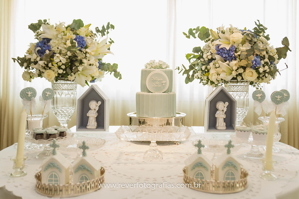 mesa de batizado decorada com doces, bolo, flores, pirulitos e vela