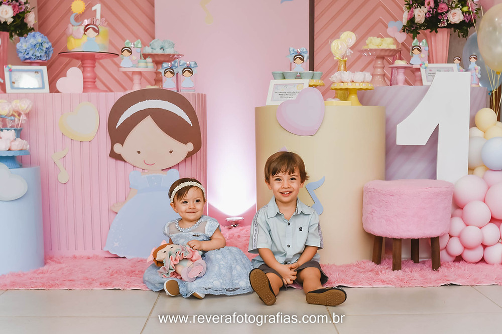 bebê e menino sentados em frente à decoração da festa de 1 ano