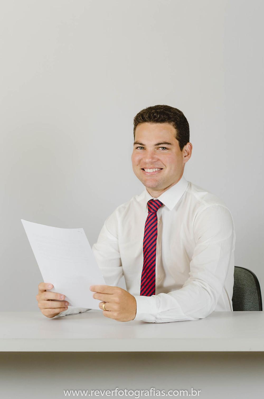 Sessão fotográfica corporativa de imagem profissional homem sentado a mesa segurando papel nas mãos
