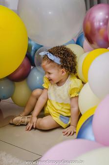 rever fotografias: foto criativa e espontanea de bebe sorrindo em meio aos balões e se escondendo de sua mãe em festa de aniversário infantil de 2 anos com tema da boneca metoo realizada no salão de festas de condominio no bairro jardins na cidade de aracaju sergipe