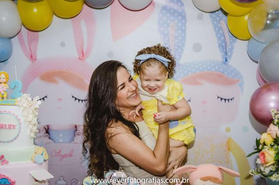 rever fotografias: fotografia espontanea de mãe segurando bebê no colo em frente a mesa do bolo em festa de aniversário infantil de 2 anos com tema da boneca metoo realizada no bairro jardins na cidade de aracaju sergipe