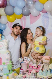 rever fotografias: fotografia espontanea de pai e mãe segurando bebê no colo em frente a mesa do bolo em festa de aniversário infantil de 2 anos com tema da boneca metoo realizada no bairro jardins na cidade de aracaju sergipe