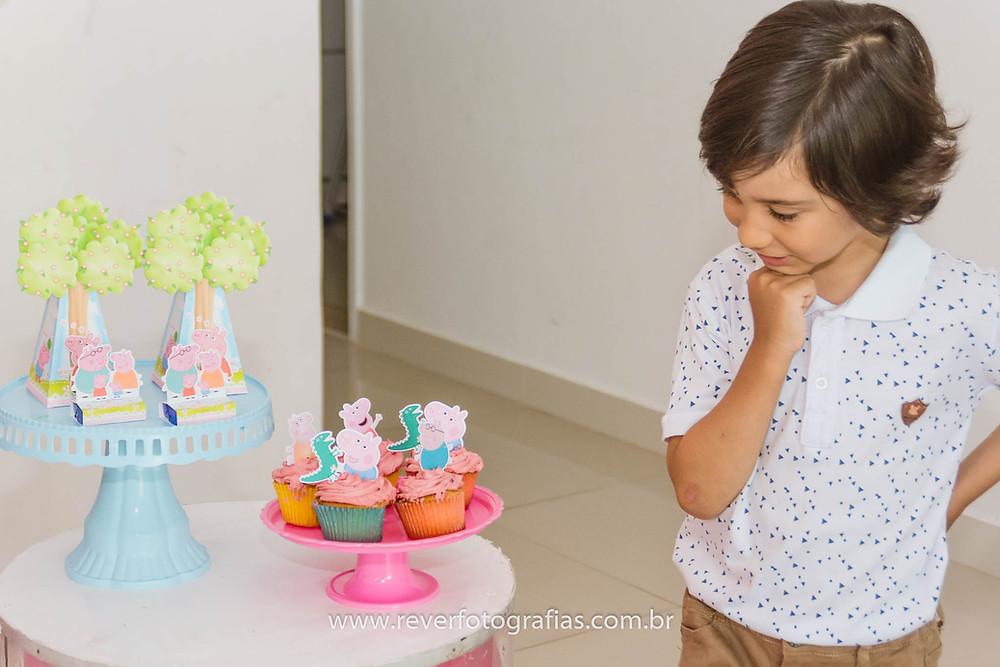 fotografia de criança olhando para decoração de festa infantil com tema da peppa pig