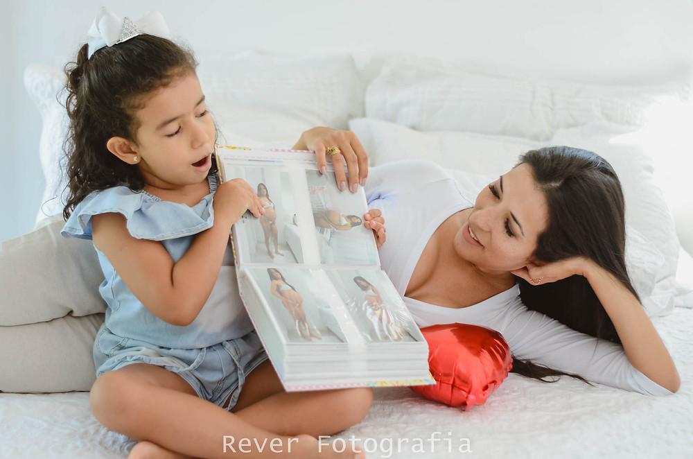 Rever Fotografias: ensaio fotográfico família mãe e filha olhando o álbum de fotos antigas no bairro jardins em aracaju-se