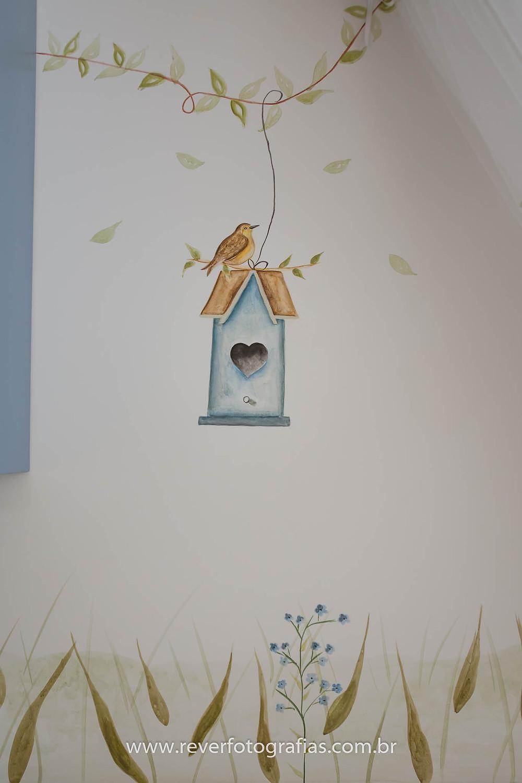 pintura artística com pássaro e folhas em parede de quarto de bebê aracaju