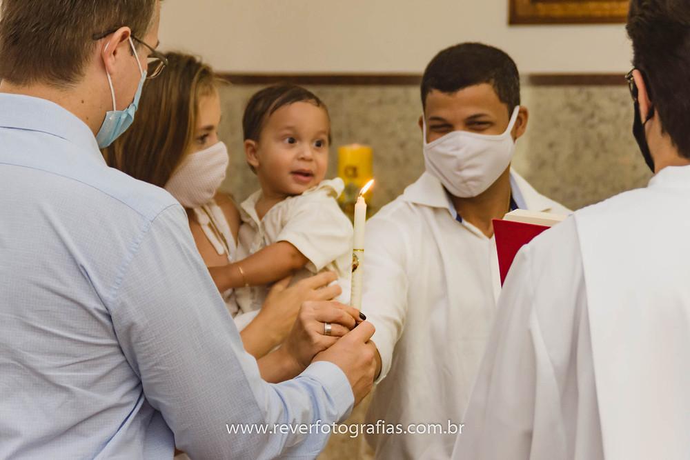 fotografia de pai e padrinho segurando vela em cerimônia de batismo em igreja de aracaju