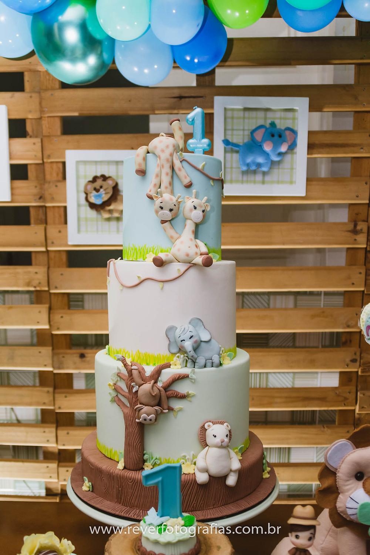 fotografia de bolo de festa infantil com três andares decorado com tema safari