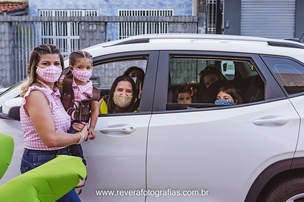 mae com filha no colo ao lado de carro com os convidados da festa infantil em formato drive thru