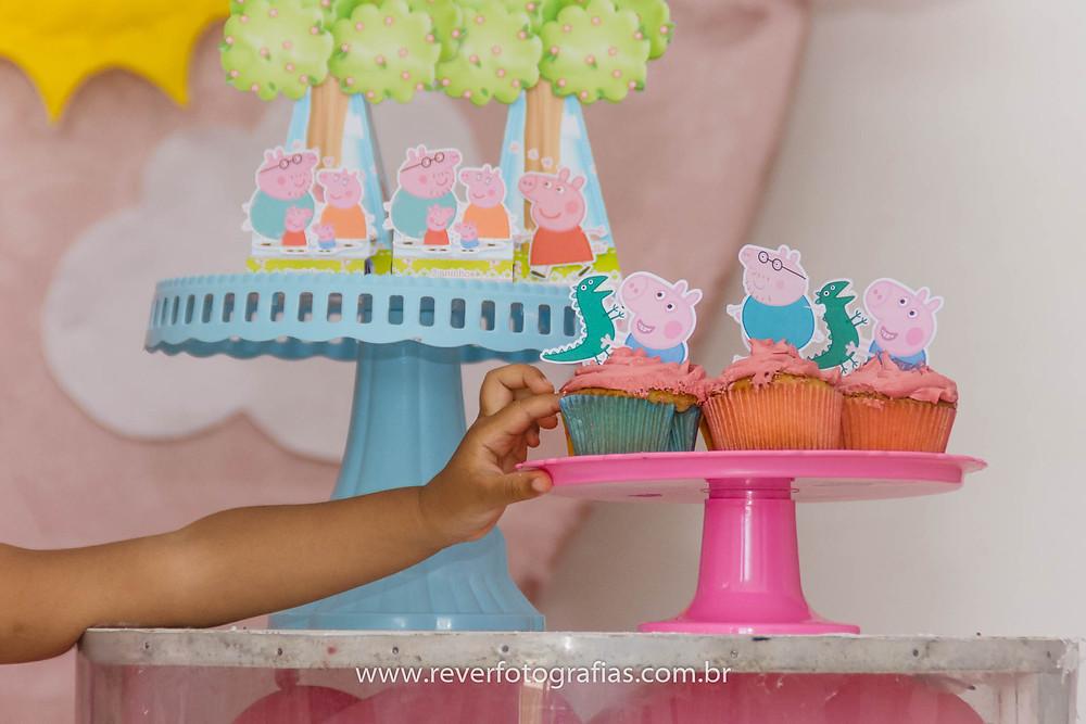 crianca colocando a mao em cupcake na festa de aniversario
