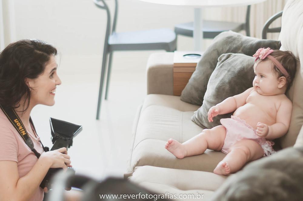 fotógrafa infantil da Rever Fotografias brincando com bebê num ensaio infantil em aracaju