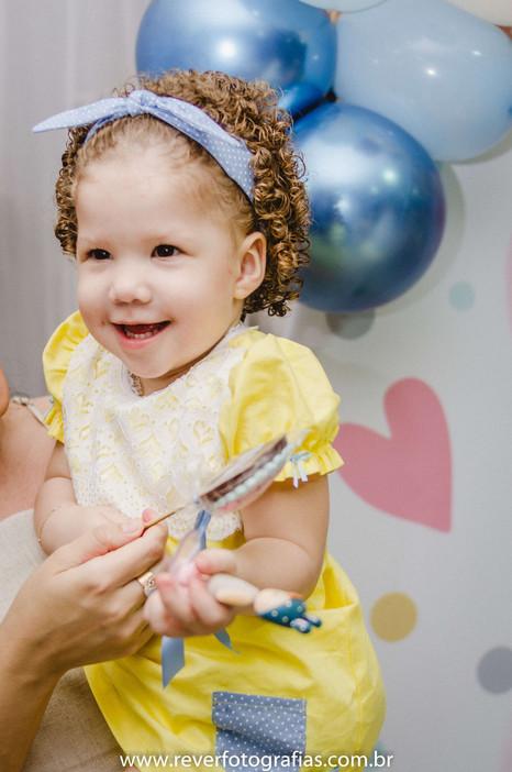 rever fotografias: foto do sorriso timido espontaneo de criança no colo da mãe em frente ao bolo em sua festa de aniversário infantil de 2 anos com tema da boneca metoo realizada no bairro jardins na cidade de aracaju sergipe