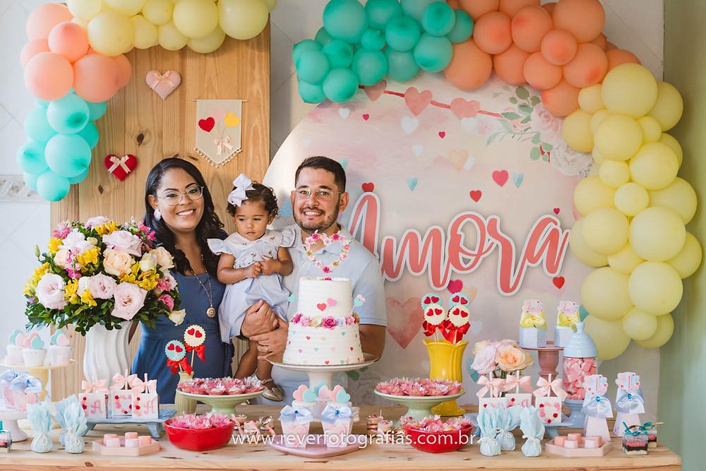 fotografia de pais segurando bebe em frente a mesa de festa de aniversario