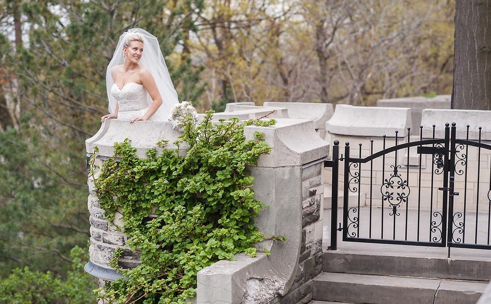 A bride behind Casa Loma at her wedding