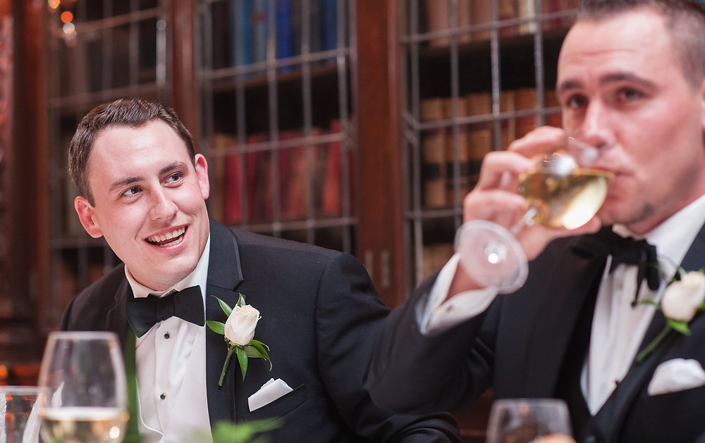 A groom laughing inside the Library at Casa Loma at their reception