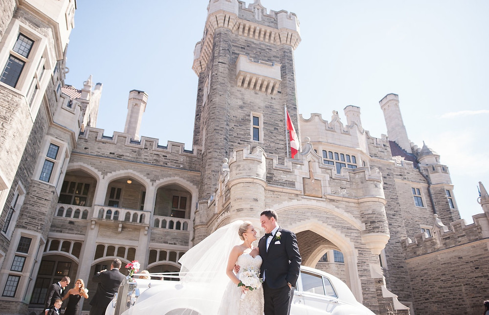 A bride and groom in front of Casa Loma