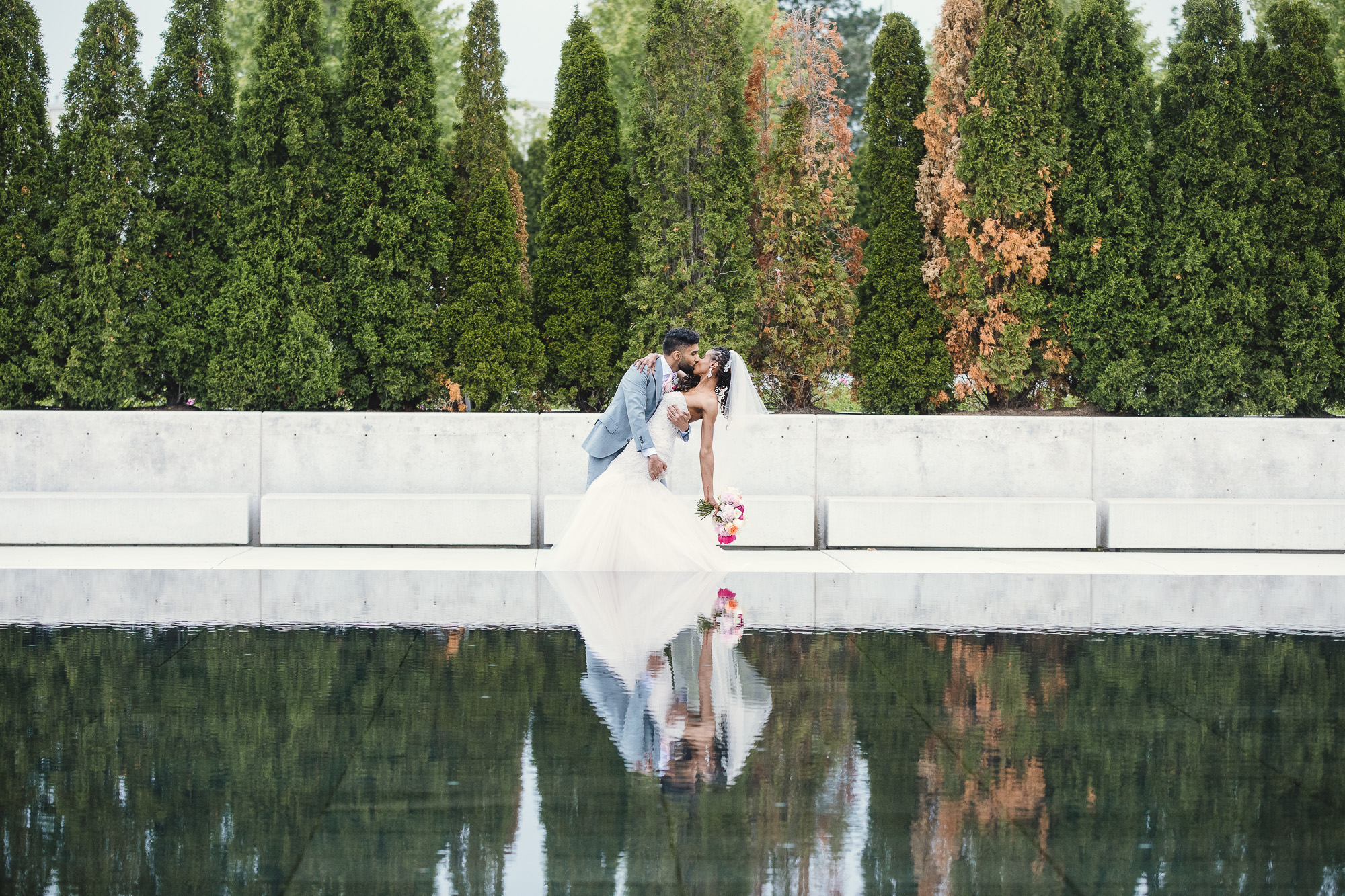 A bride and groom standing in front of the Aga Khan Museum in Toronto