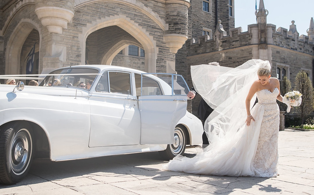 A bride leaving a Rolls Royce limousine in front of Casa Loma