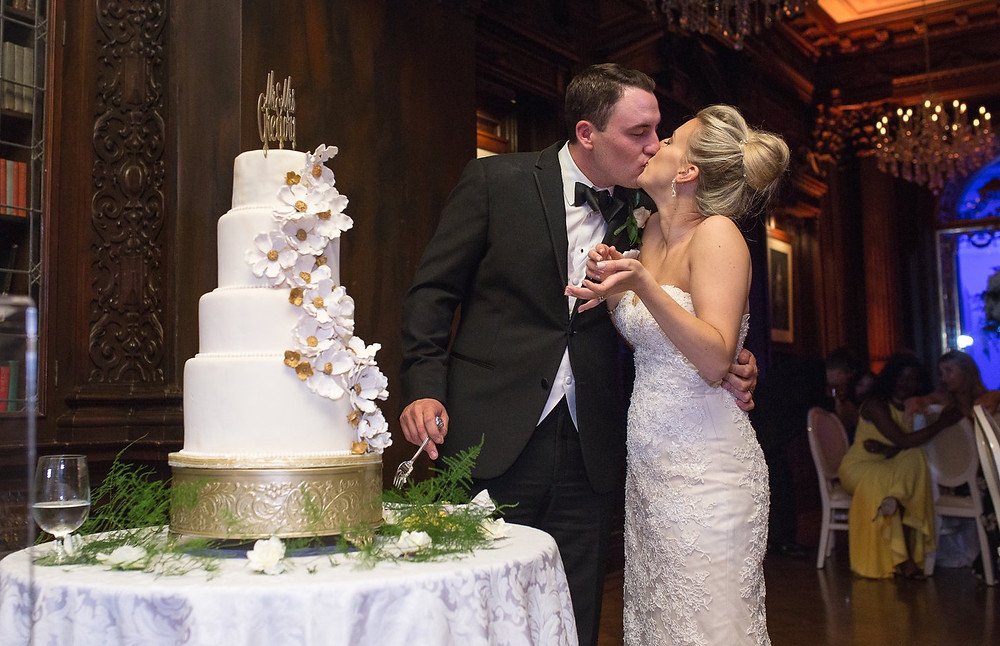 Bride and groom kissing next to their wedding cake at Casa Loma