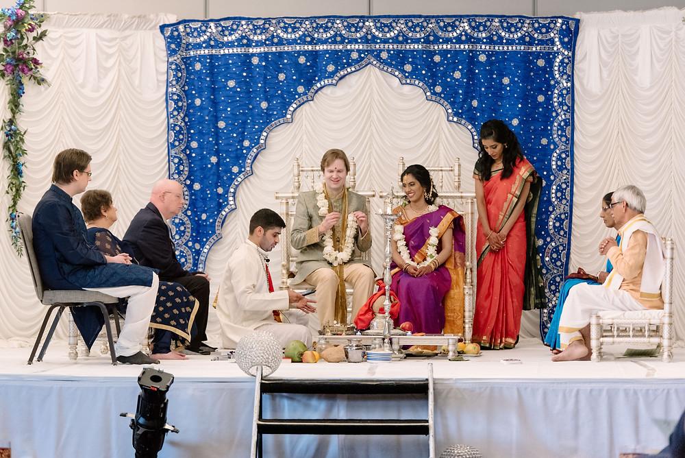 Hindu wedding ceremony with blue and ivory mandap decor.