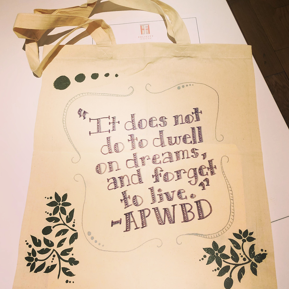"Photo of a hand-decorated tote bag, with the quote ""It does not do to dwell on dreams, and forget to live. -APWBD"""