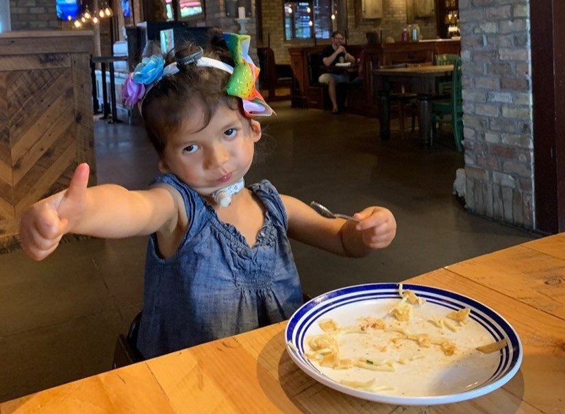G-tube fed tracheostomy child eating a meal in a restaurant.