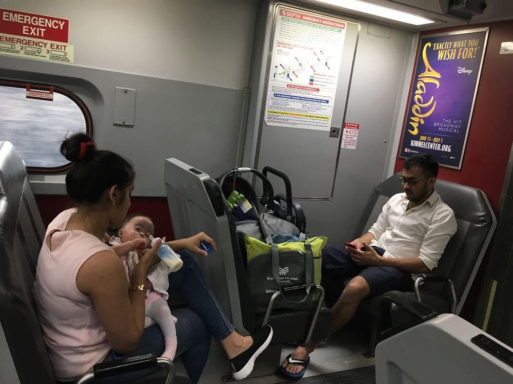 A mother feeds her infant daughter by bottle on a train.